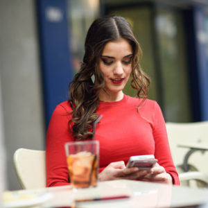 Young woman looking at her smartphone sitting in a cafe