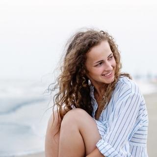 Beautiful woman sitting on beach in white shirt, smiling