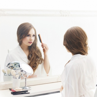 Young woman applying makeup in a studio